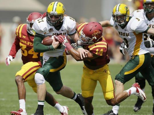 North Dakota State quarterback Carson Wentz (11) tries to break a tackle by Iowa State linebacker Jared Brackens (14) during the Aug. 30, 2014, game in Ames, Iowa.