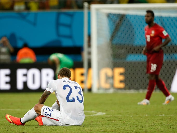 United States defender Fabian Johnson sits on the ground after the final whistle as Portugal forward Varela, who scored the tying goal, walks past.