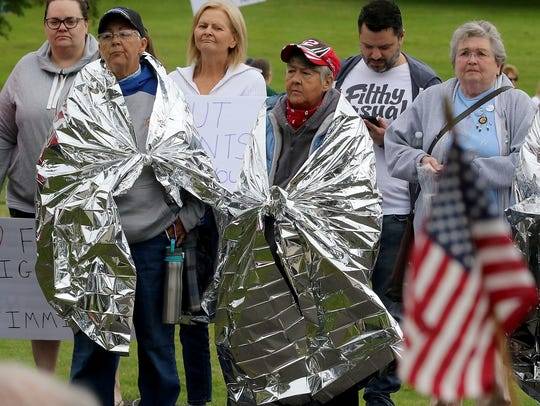 Terry Sellman, left, and Bones Edens, both of Bremerton, wear mylar blankets as they listen to the speakers during the Families Belong Together Rally in Bremerton on Saturday. They wore the blankets as a show of support to migrants who are issued the same ones upon being detained.