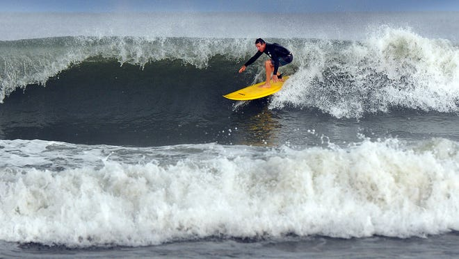 A surfer tackles high surf and swells from Hurricane Joaquin at the Cocoa Beach Pier in this 2015 file photo.