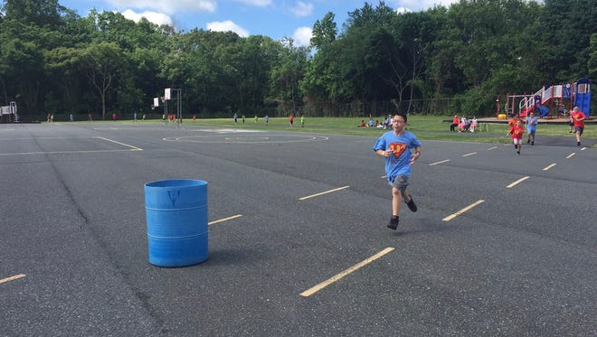 Fifth-grader Michael Rios, 12, pushes the last yards of the annual Durand Run on Friday. Blue shirts marked fifth-graders taking part in the race.