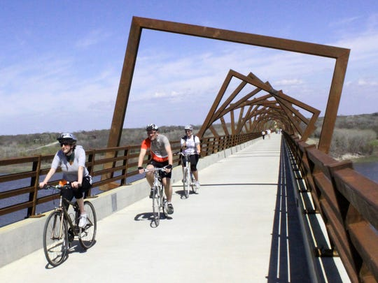 Cyclists ride west along the High Trestle Trail Bridge near Madrid in 2011.