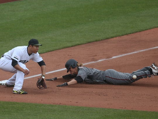 Arizona Diamondbacks starting pitcher Zack Greinke (right) slides into third base with a triple as Pittsburgh Pirates third baseman Jung Ho Kang (16) awaits the throw during the fifth inning at PNC Park.