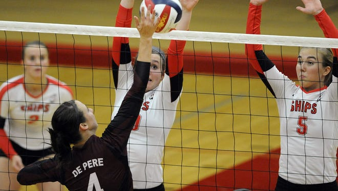 De Pere's Ashley Smits hits the ball as Manitowoc Lincoln's Mallory Dixon, left, Katie Henry, center, and Alyssa Fischer, right, prepare their defense during their volleyball game on Tuesday, Sep. 16, 2014 at Manitowoc Lincoln High School.