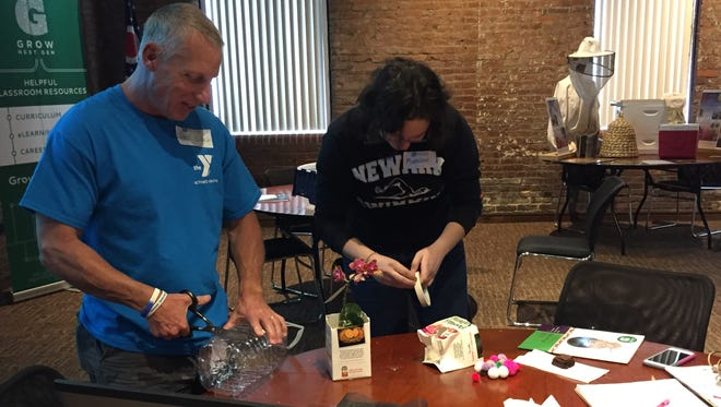 Jeffrey Baker, left, and Madeline Black, right, work on their plant packaging project Saturday.