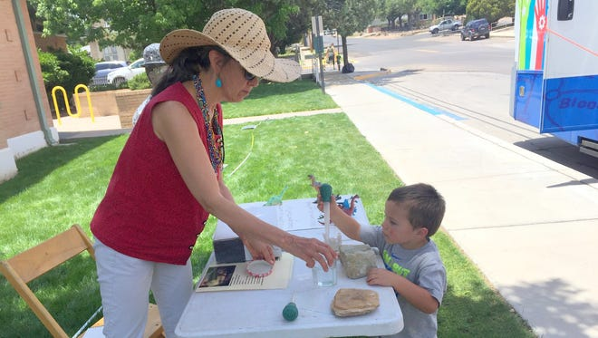 Three-year old Azton Oaxaca is shown about dinosaurs outside the Silver City Public Library by Wonders on Wheels director Jaimie Brytowski on Tuesday afternoon.