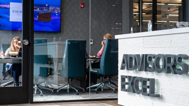 """Employees work in a conference room near the front entrance of Advisors Excel's newly renovated """"Professional Building,"""" at 4125 S.W. Gage Center Drive. On Tuesday, Advisors Excel executives offered members of the news media a tour of the company's two new office buildings at the Gage Center campus, where about 180 employees began working this year."""