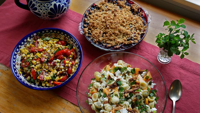 A market lunch includes Pasta Salad with Melon, Pancetta and Ricotta Salata; Corn, tomato and Basil Salad with Mustard Vinagrette and Summer Berry Crisp (Blueberry).