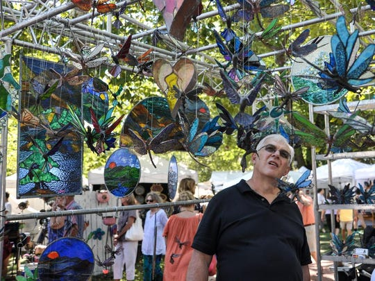 Dennis Swartzwelder of Clyde eyes some stained-glass suncatchers at a past Village Arts and Crafts Fair. It returns Aug. 3-4.