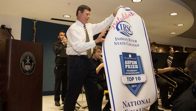 Dr. Edwin Massey, Indiean River State College president, unfurls the Aspen Top Ten National Finalist banner at a college-wide celebration.
