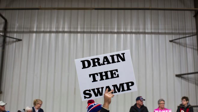 """FILE - In this Oct. 27, 2016, file photo, supporters of then-Republican presidential candidate Donald Trump hold signs during a campaign rally in Springfield, Ohio. President-elect Donald Trump's campaign promise to """"drain the swamp"""" of Washington might make it difficult for him to fill all the jobs in his administration. (AP Photo/ Evan Vucci, file)"""