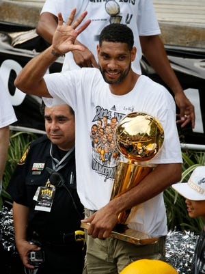 Spurs forward Tim Duncan waves to fans during the team's NBA championship parade.