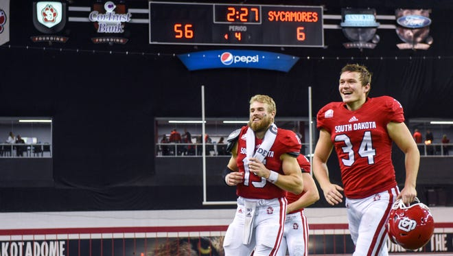 University of South Dakota quarterback Chris Streveler (15) and kicker Ethan James (34) jog off the field after defeating Indiana State 56-6 in their NCAA football game on Saturday, Oct. 14, 2017 at the DakotaDome in Vermillion, S.D.