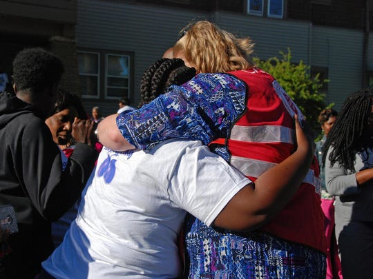 Pastor Alexis Twito (right), a chaplain, hugs Destiny Boone during a march honoring Destiny's 9-year-old daughter, Za'layia Jenkins, who was shot and killed in May 2016.
