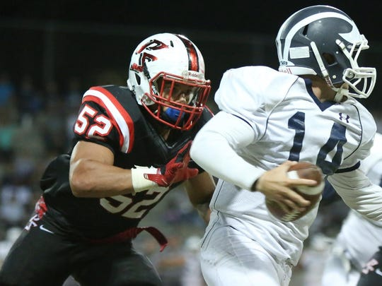 Palm Springs' Tyler Hawkins (52) prepares to tackle Redlands quarterback Joey Burrola during the first half of the game in Palm Springs on Friday night, September 4, 2015.