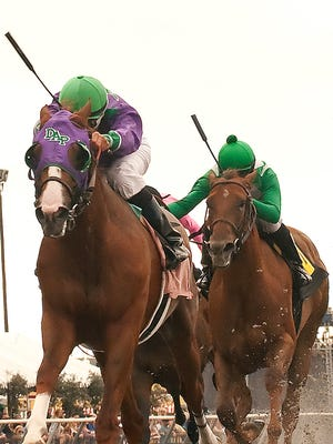 California Chrome, left, with Alberto Delgado aboard, outruns Moving Desert, right, with Joseph Talamo aboard, to win the $100,000 Graduation Stakes last July at Del Mar Thoroughbred Club in Del Mar, Calif.