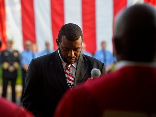 Pastor Marcus Collins bows his head in reflection during