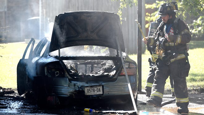 Firefighters work on a car fire in the driveway of a home on Princess Lane in Nashville on Tuesday, Sept. 27, 2016.