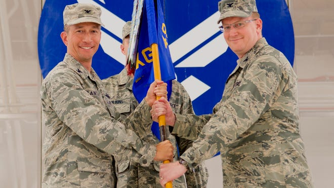 Col. Houston Cantwell, 49th Wing commander, gives the 49th Maintenance Group guidon to Col. Tim Harbor during a change of command ceremony at Holloman Air Force Base June 30.