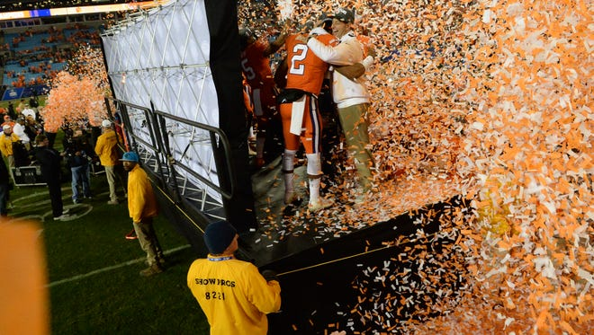 Clemson quarterback Kelly Bryant hugs coach Dabo Swinney behind a wall of confetti after the Tigers beat Miami 38-3 in the ACC football championship in Charlotte on December 2.
