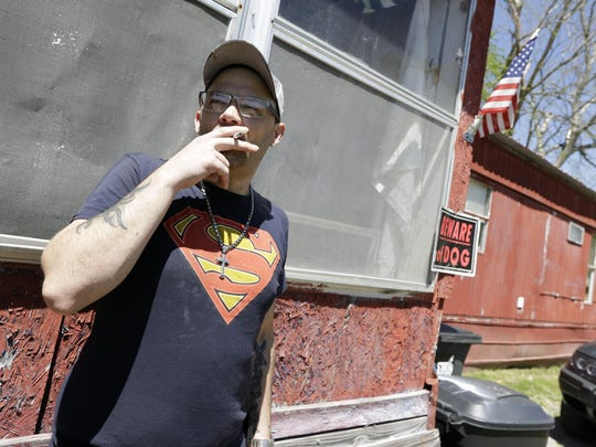 In this April 16, 2019, photo, Johnny Gibbs stands outside his family's home in Liberty, Tenn. Gibbs has been trying to get a valid driver's license for 20 years, but he can't afford it. To punish him for high school truancy in 1999, Tennessee suspended his ability to get a license until he turned 21. When Gibbs couldn't pay for traffic violations, he ended up serving jail time and probation. But rather than wiping his fines and allowing him to obtain a valid license, he wound up even more deeply in debt because he had to pay a monthly supervision fee to a private probation company. (AP Photo/Mark Humphrey)