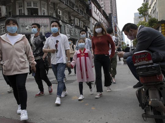 Residents walk along a retail street in Wuhan in central China's Hubei province on Wednesday, April 8, 2020. The city of 11 million people was locked down Jan. 23 to contain the coronavirus. (AP Photo/Ng Han Guan)