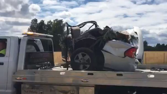 A piece of a car involved in a crash that killed three people is hauled away from the crash site near Canby Tuesday morning.