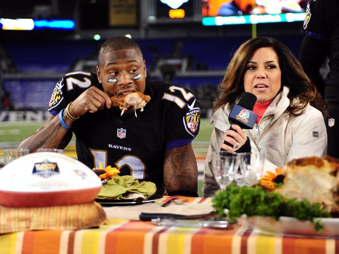 Baltimore Ravens wide receiver Jacoby Jones (12) eats a turkey leg while being interviewed by NBC personality Michele Tafoya (right) after beating the Pittsburgh Steelers 22-20 during a NFL football game on Thanksgiving at M&T Bank Stadium.