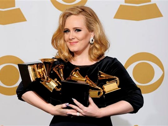 Adele poses backstage with her six awards at the 54th annual Grammy Awards on Sunday, Feb. 12, 2012 in Los Angeles.