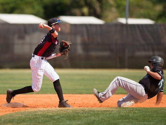 Port St. Lucie's Tyler Stone throws to first base after forcing Jensen Beach's Robert Piekarski out at second during the top of the fifth inning of the high school baseball game Tuesday, March 13, 2018, at Port St. Lucie High School.