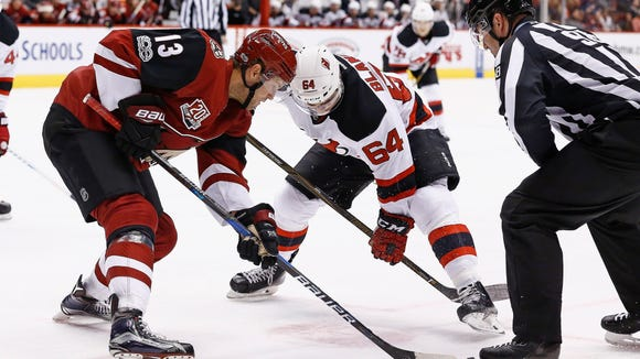 Arizona Coyotes center Peter Holland (13) wins a face off against New Jersey Devils left wing Joseph Blandisi (64) during the first period of an NHL hockey game Saturday, March 11, 2017, in Glendale, Ariz. The Coyotes defeated the Devils 5-4. (AP Photo/Ross D. Franklin)