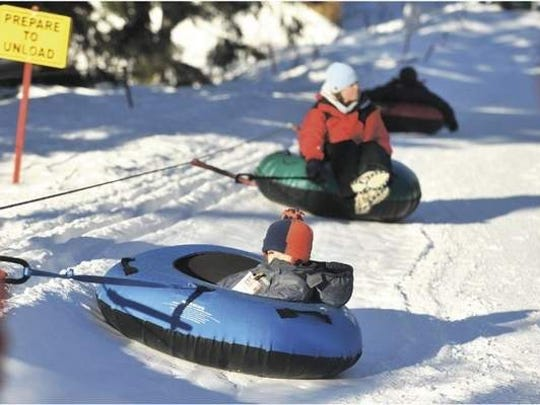 Inga Idzal of Gearhart and her 3-year-old son, Diego Sanchez, use the rope tow lift at the Skibowl on Dec. 26. The resort offers a tubing run for young children and a steeper, longer run for older children, teens and adults.