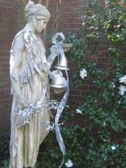 A statue draped in silver decorations at ELsong Gardens.