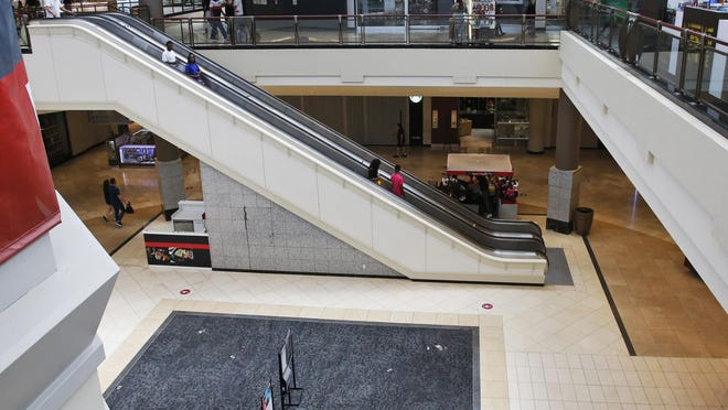FILE - In this May 1, 2020, file photo, people ride down an escalator at a shopping mall in Oklahoma City as it reopens from its closure since mid-March due to coronavirus concerns. Many businesses are requiring customers and workers to sign forms saying they won't sue if they catch COVID-19. Businesses are afraid they could face lawsuits even if they follow social distancing and other government guidelines as they reopen across the U.S. after coronavirus shutdowns.