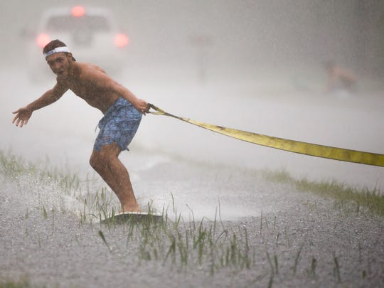 Thomas Santangelo, 17, skim boards along a flooded ditch next to Old Livingston Way as steady rains continued throughout the day across Collier County Aug. 27, 2017, in North Naples.