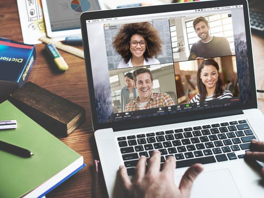 A person on a laptop videoconferencing with four other people.