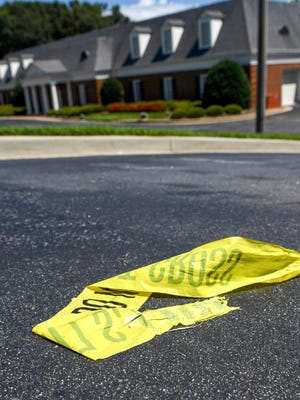 Crime tape remains at the edge of the Thomas McAfee Funeral Home, at 6710 White Horse Road, in the Berea community on Saturday.
