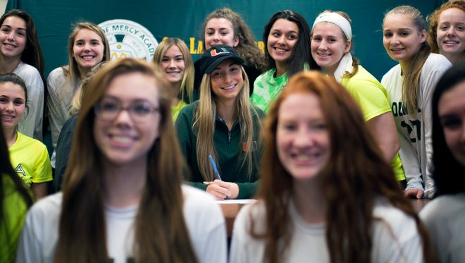 Our Lady of Mercy's Tia Dupont poses with teammates as she celebrates an offer to play soccer for the University of Miami Friday, Feb. 3 in Newfield.