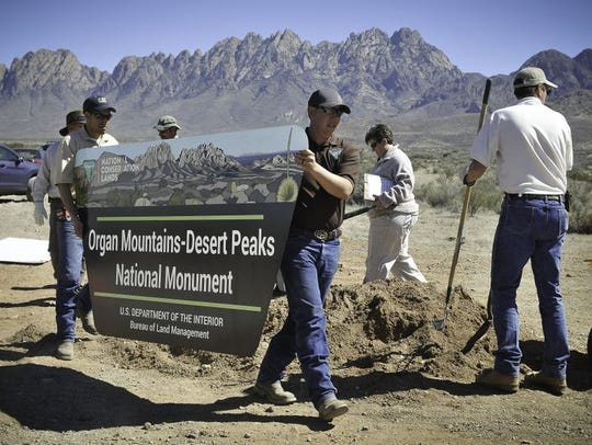 Workers install a sign at the new Organ Mountain-Desert