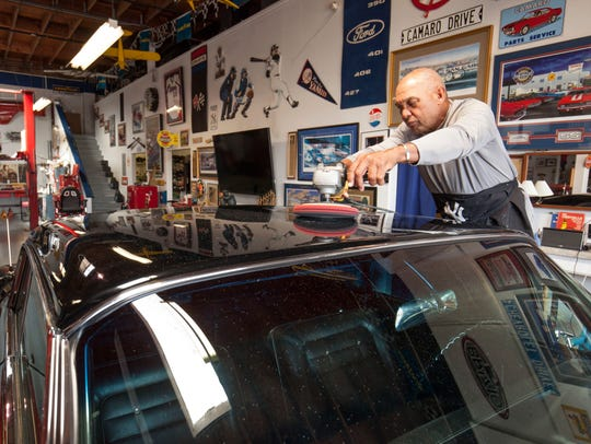 Reggie Jackson buffs one of his cars in his  garage.