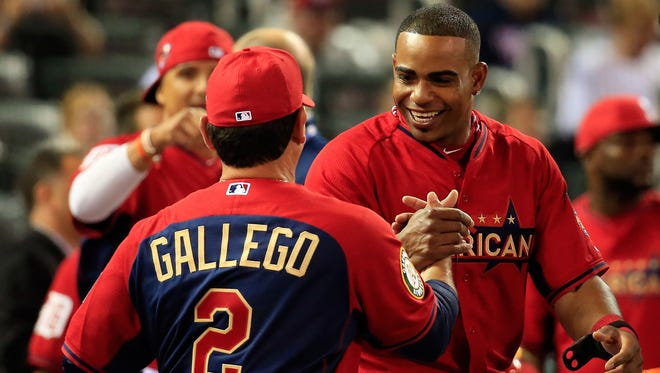 American League All-Star Yoenis Cespedes of the Oakland Athletics celebrates with coach Mike Gallego, who threw to him in the competition, after winning the home run derby on Monday night.