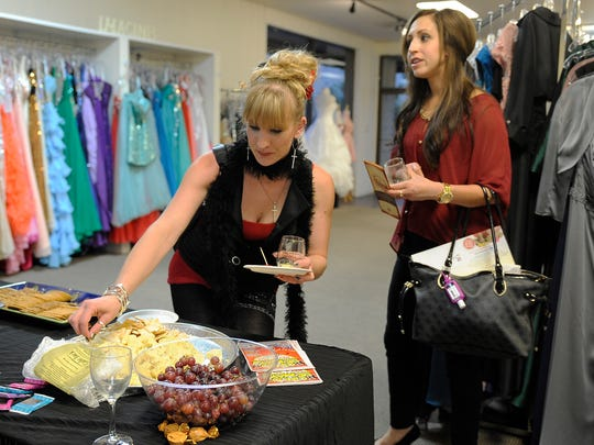 Sarah Eggman (left) and Lacee Solis get some wine and cheese at Anabelle's Bridal Boutique during the Wine & Cheese Walk in downtown Visalia.