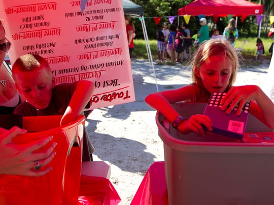Bobbie Summers, left, helps her son Peyton, 7, and daughter Emily, 10, pick out school supplies at the Kids in the Kitchen event on Oct. 18 in south Fort Myers. Taste of the Town helps the Junior League fund community outreach events like Kids in the Kitchen.
