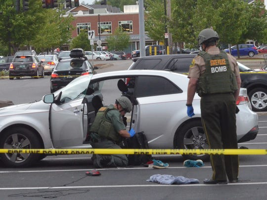 Members of the Vermont State Police bomb squad investigate a Kia sedan that was the site of a pipe bomb explosion June 8, 2016,  on the road before pulling into the Shelburne Road Plaza parking lot in Burlington.