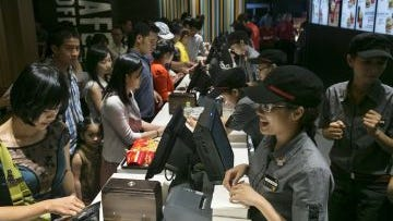 People wait in line to purchase food at a new McDonald's restaurant in Ho Chi Minh on Feb 14, 2014.