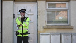 A police officer stands on duty outside a residential
