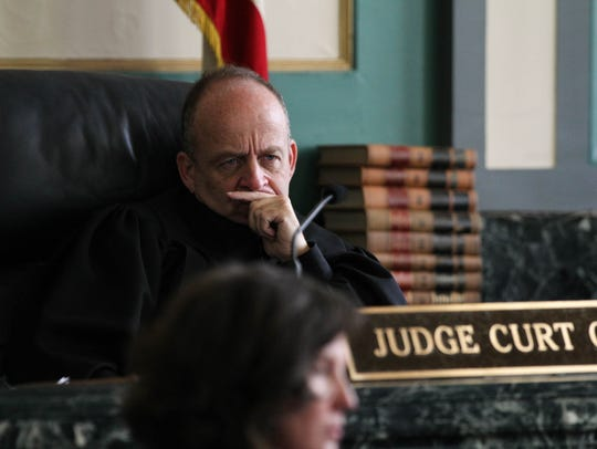 Judge Curt Hartman listens to a statement from Monika