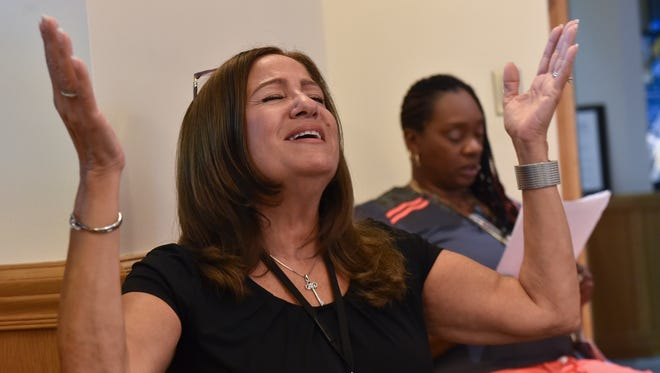 """Billie Jo D'Ambrosio, volunteer at Indian River Medical Center, gives praise during a prayer service in the hospital's chapel on Thursday, Oct. 5, 2017, for all those affected by the recent hurricanes, earthquake and the shootings in Las Vegas. """"In a time like this, we just need to all come together, doesn't matter about denomination,"""" D'Ambrosio said. """"It just means were going to see others in unity, and that's what God wants, us to love our brother and our sister in unity."""""""