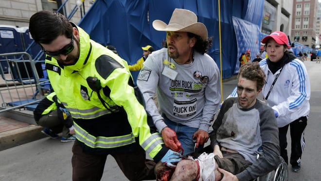 An emergency responder and volunteers, including Carlos Arredondo, center, in the cowboy hat, push Jeff Bauman in a wheelchair after he was injured in an explosion near the finish line of the Boston Marathon in 2013.