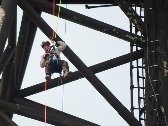 Shaun Golden, a firefighter with the Hamilton Township Fire Department, rappels from an upper deck of the Battleship New Jersey as he takes part in NSR Solutions LLC and Med-Tech's Confined Space Training classes Friday.